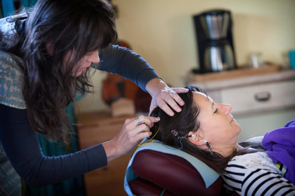 Concussion clinic technician putting neurofeedback electrodes on women's head.