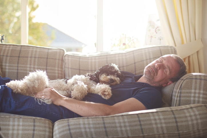 Man resting on a couch after a concussion with his little dog laying on top of him