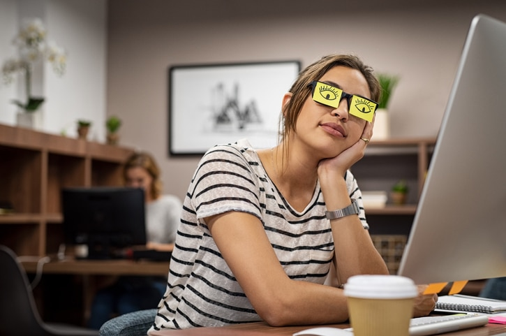 Women feels tried after a concussion. Puts post-it notes over eye to look awake.