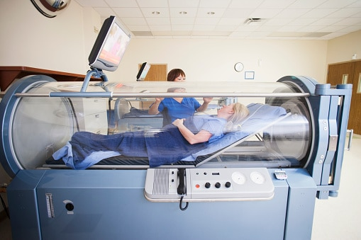 Client laying in hyperbaric oxygen chamber