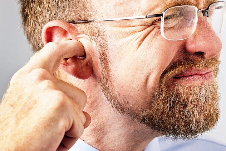 Man pressing fingers into his ear because it is ringing.