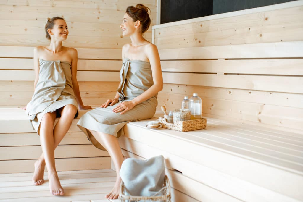 Two young girlfriends sitting and talking together while relaxing in the sauna